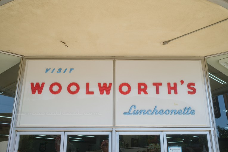 """A large white plastic sign sits above the doorway to the antique mall. Small blue letters read """"Visit"""" followed by large red letters reading """"Woolorth's"""" and then below in smaller blue script reads """"Luncheonette"""""""