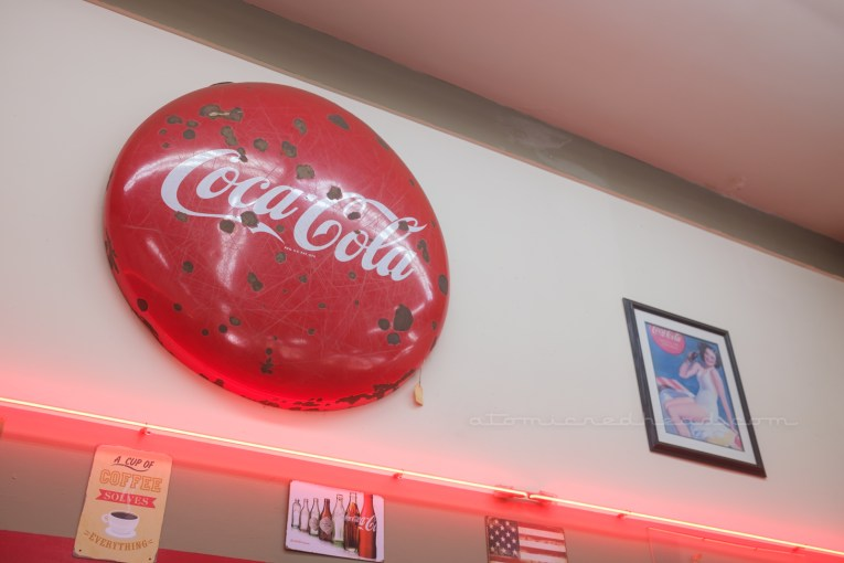 """A large circular sign reads """"Coca-Cola"""" in their famous white script hangs above a stripe of red neon."""