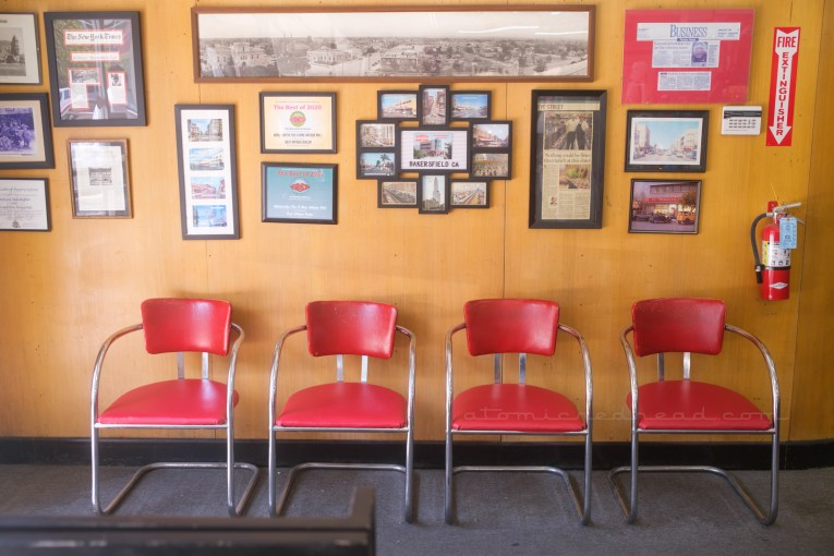 A pale wood paneled wall features framed articles, awards, and photos of the Woolworth's through the years, red upholstered and chrome chairs sit against the wall.