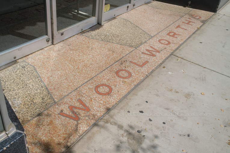 """Cream, brown and red terrazzo reads """"Woolworth's"""" outside the front doors."""