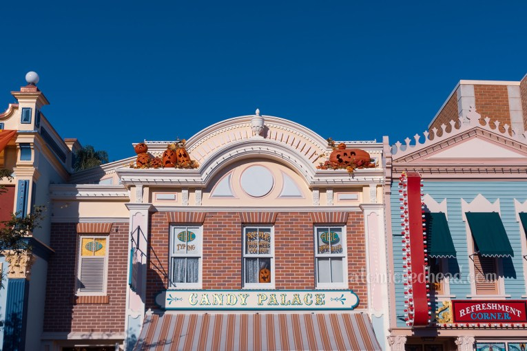 """Exterior shot of the upper floor of the Candy Palace, a brick building with some pink details. Two ledges near the top have several carved Jack O'lanterns. Above a striped awning is a sign reading """"Candy Palace"""" in gold letters."""