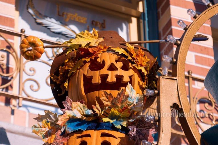 A goofy faced Jack O'lantern wears a brown hat with an arrow through the front.