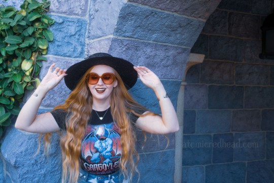 """Myself, wearing a black straw hat, black tee featuring Goliath, a massive gargoyle, and gothic script reading """"Gargoyles"""" below, hands on my hat, standing in front of the stone walls of Sleeping Beauty Castle."""