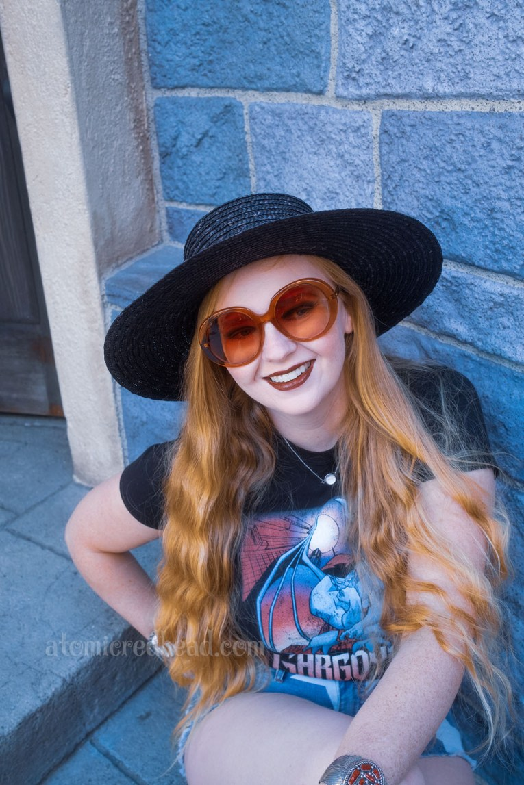 """Myself, wearing a black straw hat, black tee featuring Goliath, a massive gargoyle, and gothic script reading """"Gargoyles"""" below, and jean shorts with white stars on them, sitting in front of the stone walls of Sleeping Beauty Castle."""