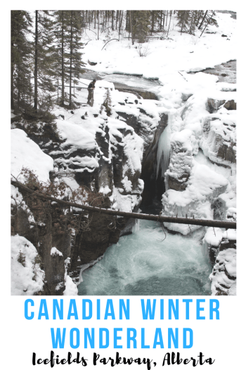 Pinnable Image of man in winter gear stands overlooking flowing rocky waterfall that is surrounded with snow in Canadian Winter Wonderland Sunwapta Falls