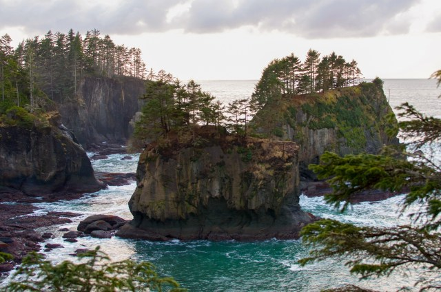 Multiple wide sea stacks surrounded by churning blue water on Olympic Peninsula