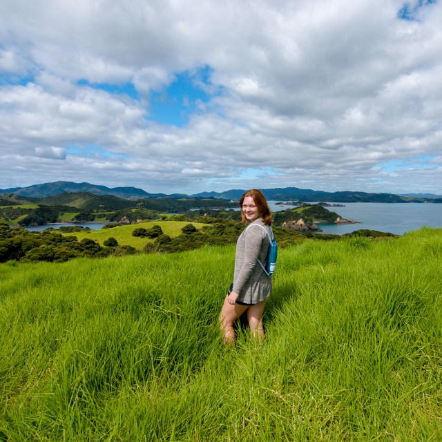 Woman facing the camera with her body faved away, standing in tall green grass overlooking chains of islands