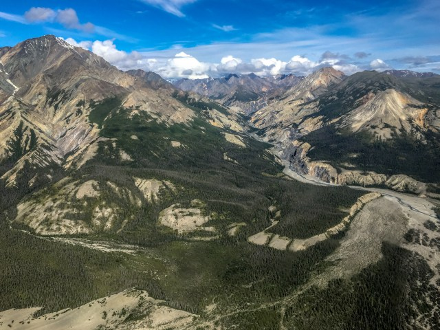 Aerial view of tall mountains spread out over forested area