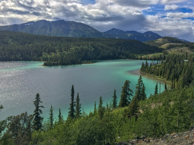 Lake with rings of emerald hue along the edges, surrounded by forests and mountains