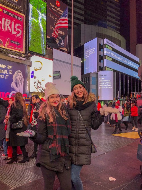 Two girls posing in front of famous Times Square billboards. There are people all around them, and they are wearing Winter jackets
