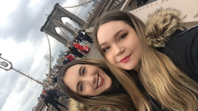 Two girls, one brunette and one blonde, standing in front of The Brooklyn Bridge, filled with pedestrians
