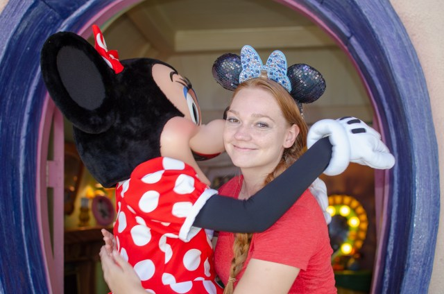 Woman dressed in red with blue Minnie ears, hugging Minnie Mouse