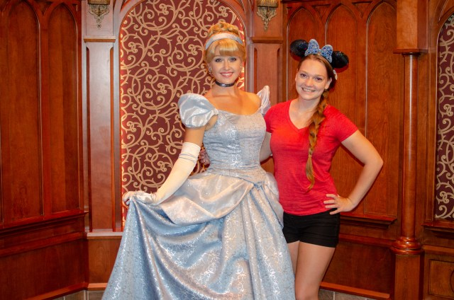 Cinderella in blue ball gown posing next to woman in red with blue Minnie ears