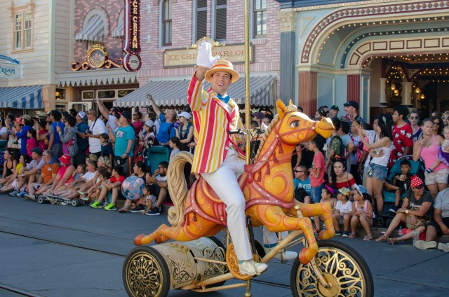 Man dressed in suit and hat, riding upon a life sized carousel horse