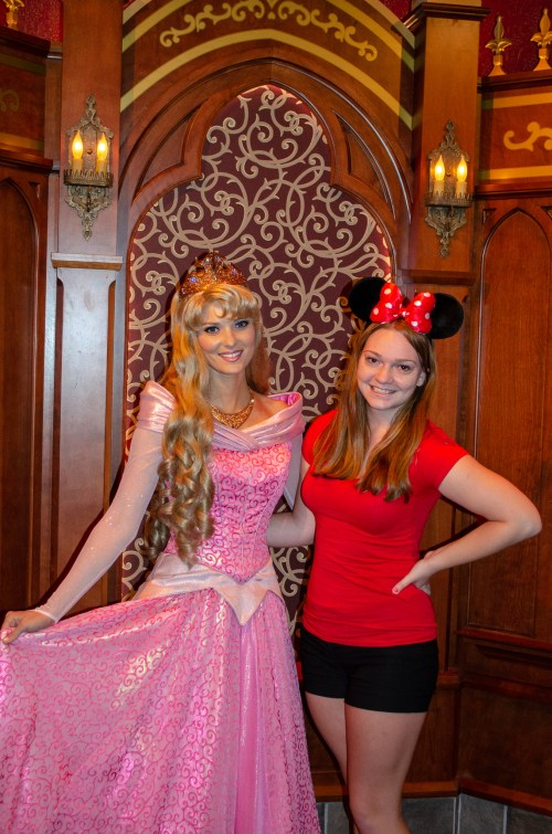 Woman in red and Minnie ears standing beside Sleeping Beauty in a hall