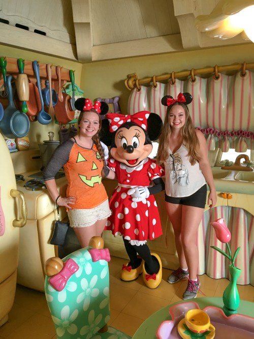 Two women, one in Halloween pumpkin shirt and one in Cinderella shirt, both with Minnie in her kitchen