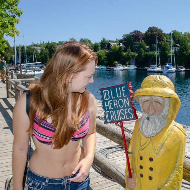 "Woman in bathing suit and shorts looking at lilfe-size fisher figurine with a sign that reads ""Blue Heron Cruises"""