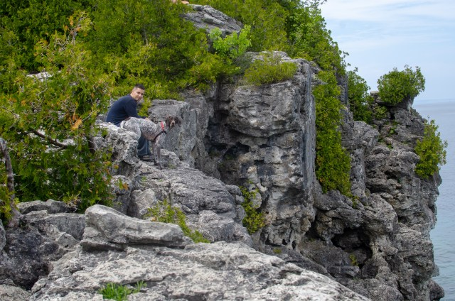 Man in long sleeved shirt and pants, and his dog, blending in to the rocky cliffs