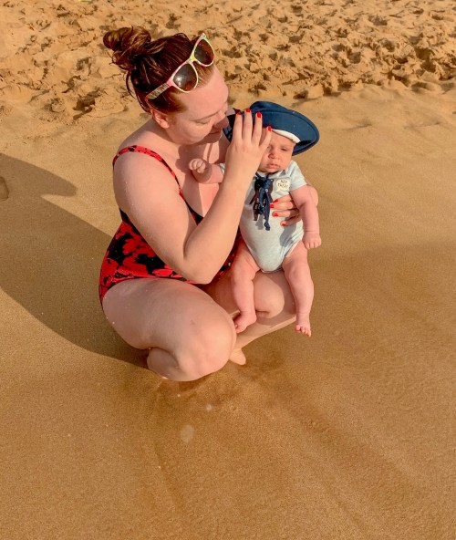 Woman holding baby at edge of water on a golden sand beach