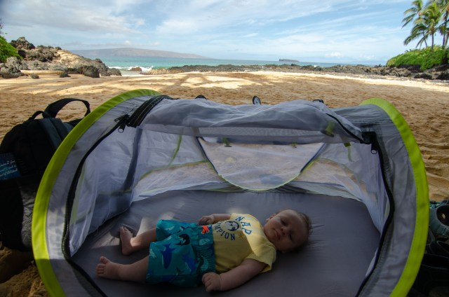 Baby sleeping in pop-up tent, on a beach with water and sand in the background
