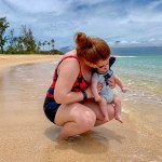Woman holding her baby beside the ocean