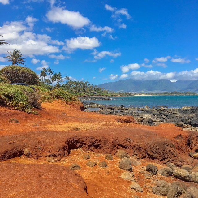 Red dirt and rocks at the edge of the ocean, with mountains in the background