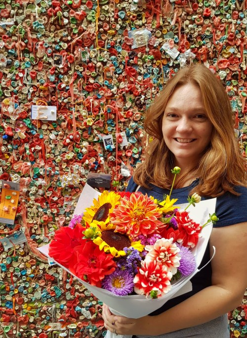 Woman holding bouquet, against a wall filled with chewed gum
