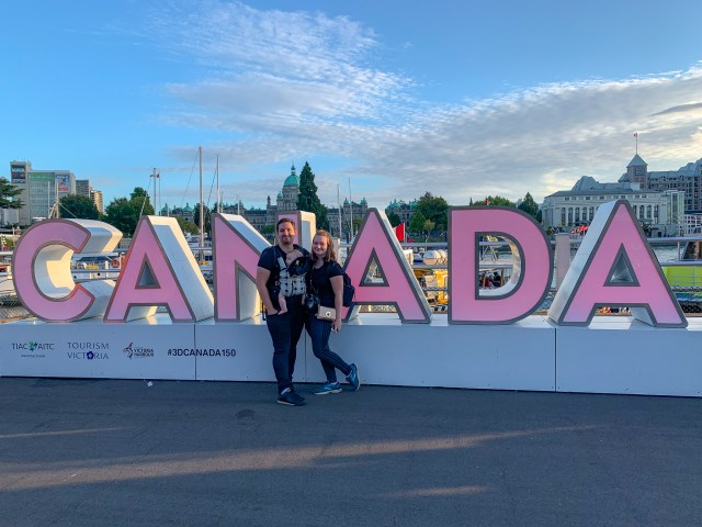 Man, woman and baby standing in front of a pink sign that reads CANADA in 3D letters
