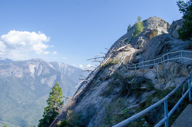 Tight staircase winding up uneven rock that overlooks mountains in the distance