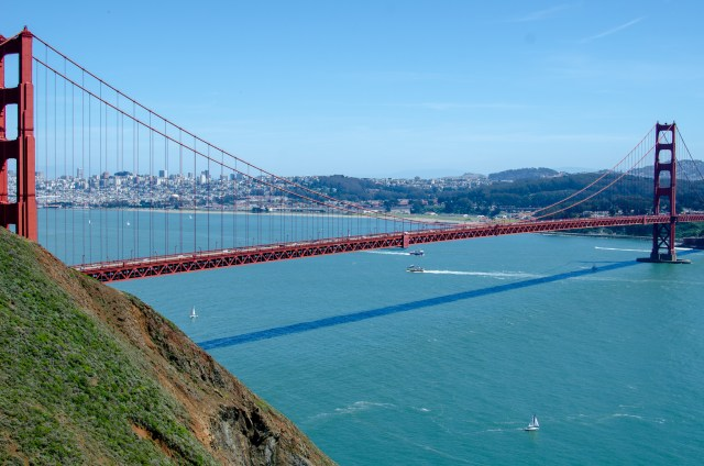 Blue ocean with the red Golden Gate bridge and a city skyline in the background