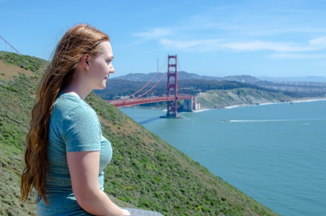 Woman with long, red hair in a green shirt looking out towards the water, with the red Golden Gate bridge in the background