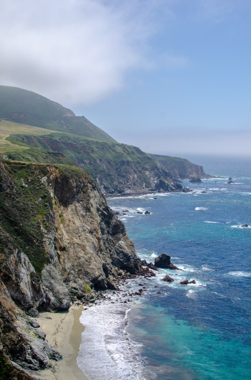 Bright blue ocean water crashes against the shore, next to rocky cliffs with greenery. There is a misty sea fog