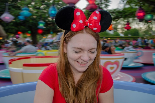 Woman in red shirt with red Minnie Mouse ears laughing with her eyes closed, while riding teacups at Disneyland, one of the top places to visit in California