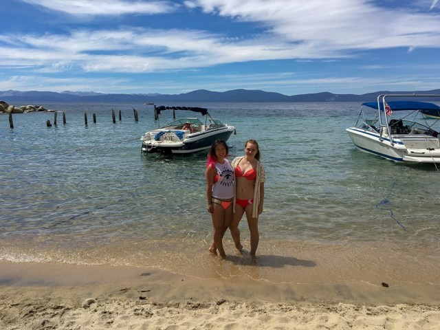 Two girls in bikinis standing on a beach in front of crystal clear water, with boats in the background