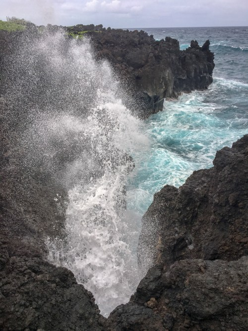 Water blowing through a crevice on a cliff, with stormy waves crashing behind it