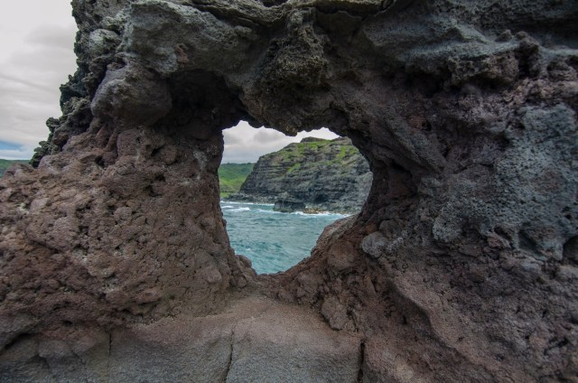 Heart shaped cut out in lava rock, with blue ocean and more lava rocks seen through the hole