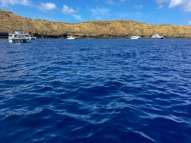 Deep blue water and boats parked just off Molokini Crater