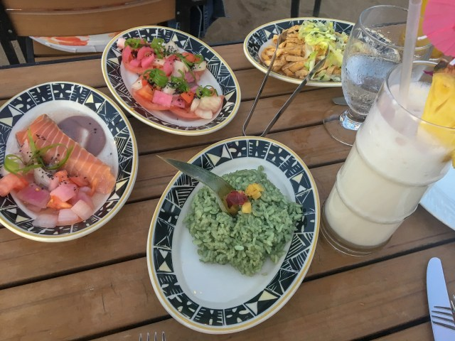 Plates of food from different Pacific Island Nations and a pina colada