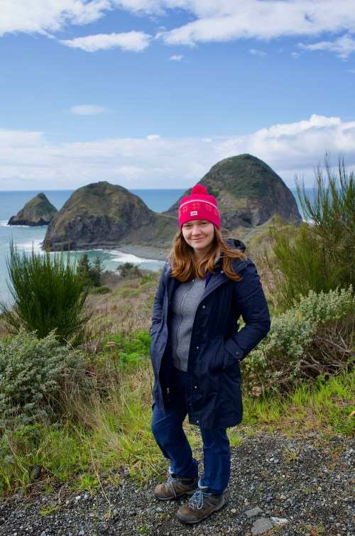 A woman dressed in gray and blue, with a pink hat, overlooking the ocean and three large rock formations
