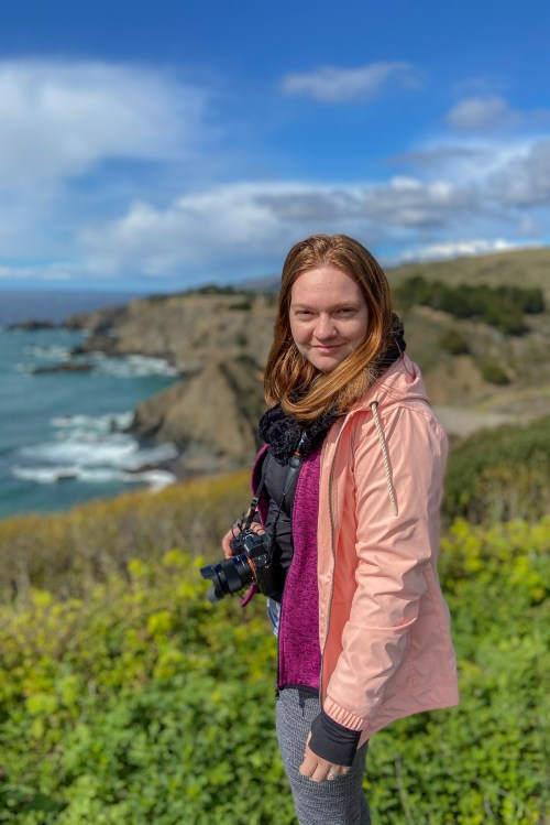 A woman in pink and gray, with a camera around her neck, looks at the camera. In the background there is greeney, cliffs and the ocean