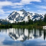 Mountain with snow covering parts of it, reflecting in a lake. Around it are evergreen trees and a blue sky with some clouds