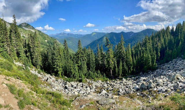 Panoramic view of one of the best hikes in Washington, looking out from Pacific Crest Trail. There is a boulder field, evergreen and layers of mountains in the distance