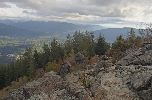 Looking out at mountains in the distance, from a rocky cliff edge lined by trees