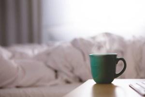 朝のベッドとコーヒーの写真