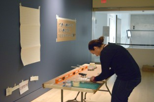 Paula installs the exhibition title lettering.