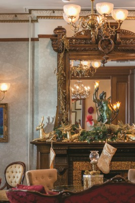 The music room's fireplace mantel extends to the ceiling and includes a lion carved into the arched woodwork across the top.