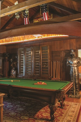 Displaying an impressive collection of curiosities, including a suit of armor, old slot machine and cowboy holster, the billiard room's dark paneling and vaulted ceiling are a dramatic backdrop to a vintage canoe turned chandelier hung over the pool table.