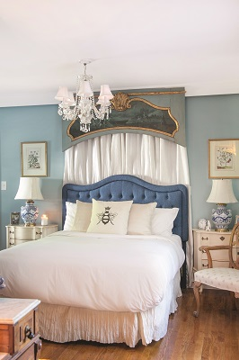 The master bedroom includes a touch of elegance with a dramatic cornice over the bed, soft linens, pretty lighting and a fireplace (not shown).