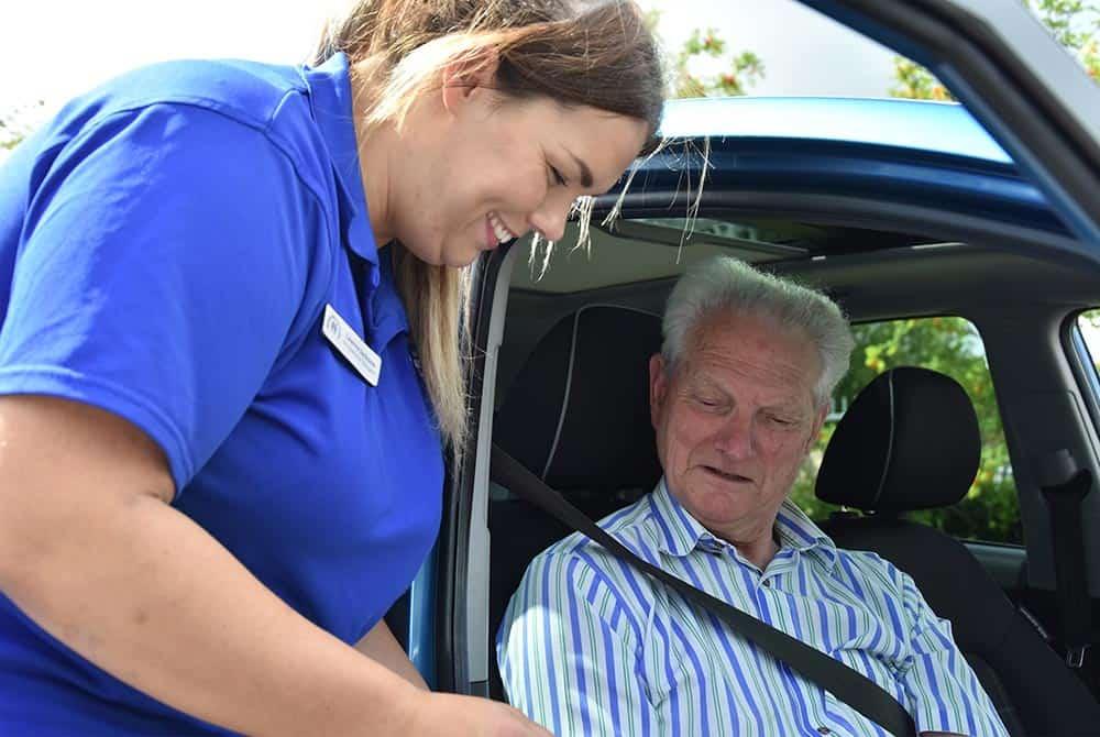 Woman assisting elderly man in car