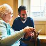 Older woman and care worker using tablet image